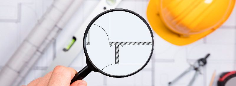Close-up Of An Engineer Examining The Architectural Blueprint With Magnifying Glass At Workplace